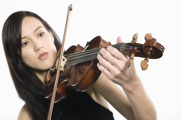Young Asian woman concentrates on playing the violin
