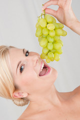 Young healthy smiling woman with white grapes