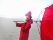 Cute teenage girl in a red raincoat with an umbrella at the beac