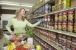 Mature woman selects tinned goods in supermarket aisle