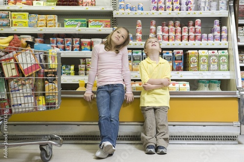Brother and sister sit side by side on fridge counter in supermarket