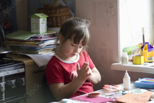 Young girl sits picking glue from her hands at workdesk