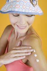 A Young Woman Rubbing Suntan Cream Into Her Arm