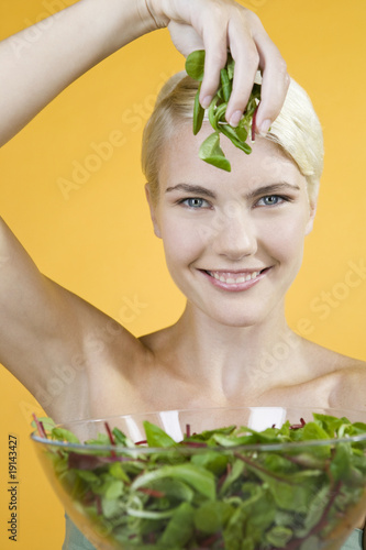 A Young Woman Holding A Bowl Of Salad