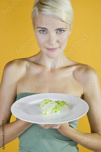 A Young Woman With A Piece Of Lettuce On A Plate