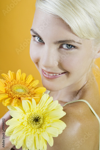 A Young Woman With An Orange And A Yellow Flower