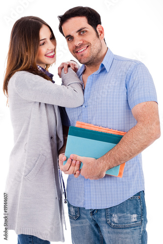 Girl looking at her boyfriend by her hands on his shoulders