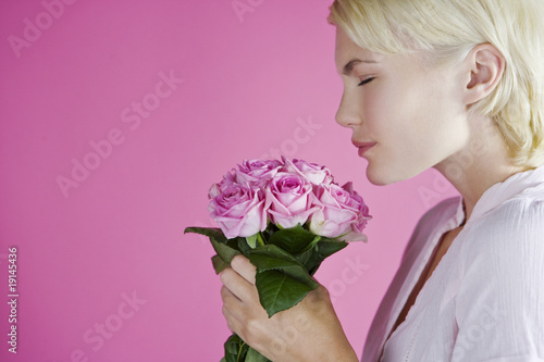 A Young Woman Smelling A Bunch Of Pink Roses