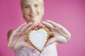 A Young Woman Holding Out A Heart Shaped Biscuit