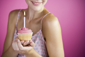 A Young Woman Holding A Birthday Cake With A Candle