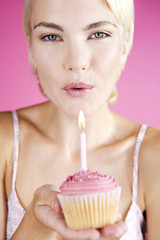 A Young Woman Blowing Out The Candle On A Birthday Cake