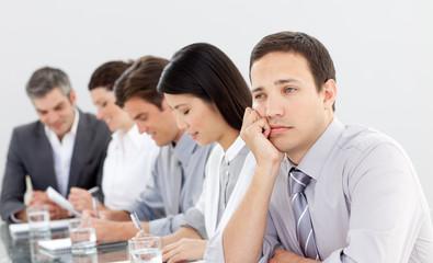 Attractive businessman bored at a presentation