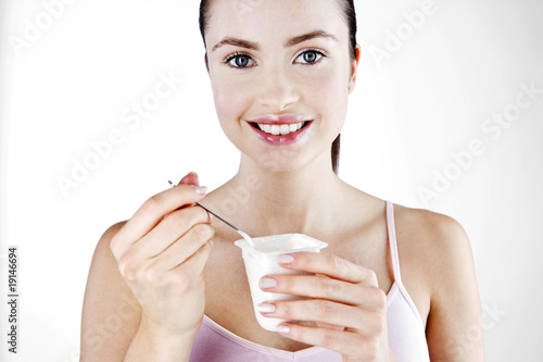 A Young Woman Eating A Yoghurt
