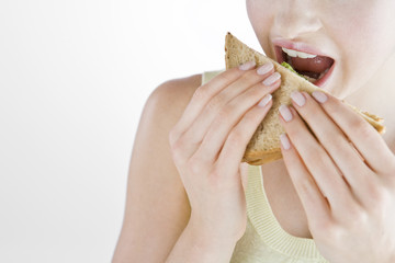 A Young Woman Eating A Sandwich