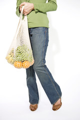 A Young Woman Carrying Vegetables In A Shopping Bag