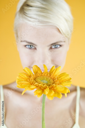 A Young Woman Holding An Orange Flower