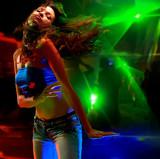 Beautiful young woman dancing in the nightclub poster