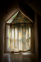 old cottage window with light creeping in behind the curtain