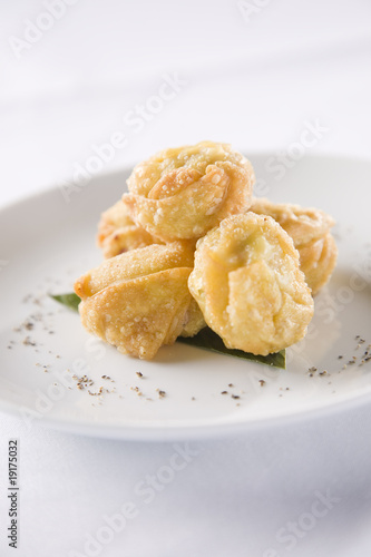 Five curry puffs on white plate.