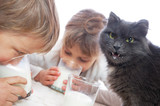 children and cat drinking milk