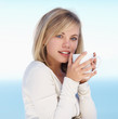 Cute female having a cup of coffee against the blue sky