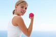 Happy fit woman with a pink dumbbell , exercising outside