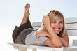 Cute happy woman lying on a wooden bench