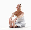 Fit young woman stretching isolated on white , laughing