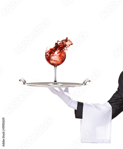 A butler holding a silver tray with wine glass