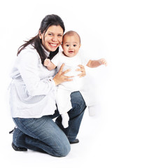 Happy mother kneeling holding smiling baby