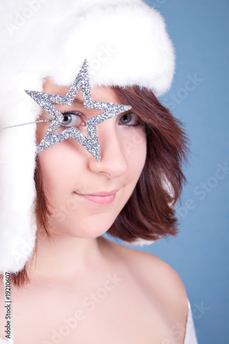 cute girl in white hat looking through a star