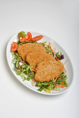 breaded fish steak on a plate with vegetable