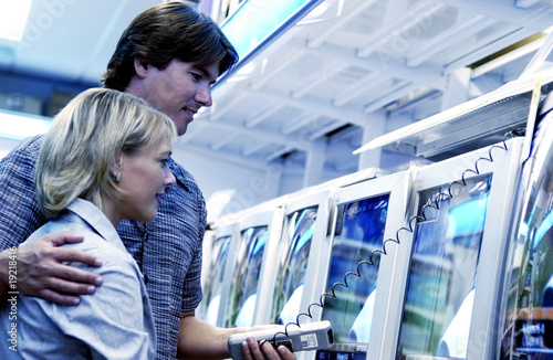 Couple looking at televisions