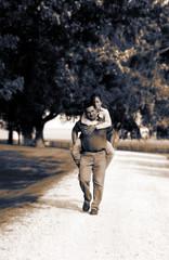 Man carrying woman piggyback down country lane