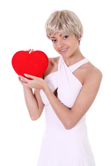 young woman holding a red heart over white background