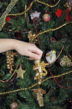 Detail of a girl hand decorating a Christmas tree