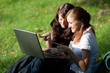 two girls with laptop working on a grass