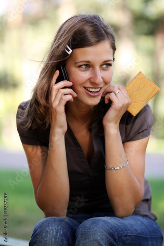 Happy young lady talking on mobile phone