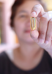 woman showing a yellow pill
