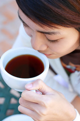 young lady drinking a cup of coffee