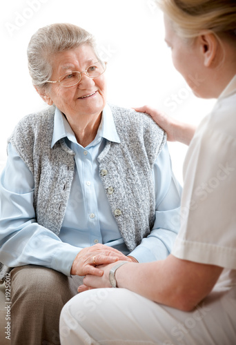 Senior woman is visited  by her doctor or caregiver at home