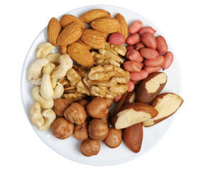 Set of nuts on a white plate, isolation