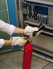 extinguisher in hands in mitten