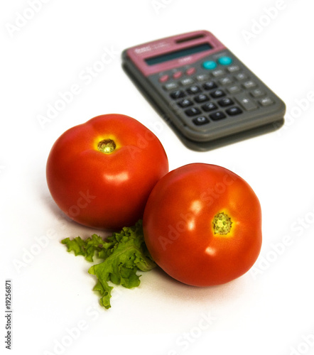 two tomatoes in front, calculator blurred in background