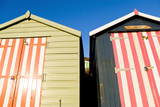 A colour landscape photo of two colourful beach huts