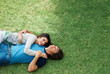Top view of a happy young couple lying on grass