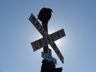 Railway crossing sign against the sun