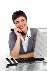 Joyful Businesswoman holding a telephone at her desk