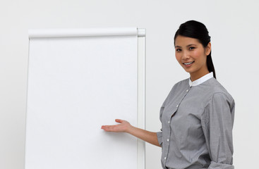 Self-assured asian female executive pointing at a board