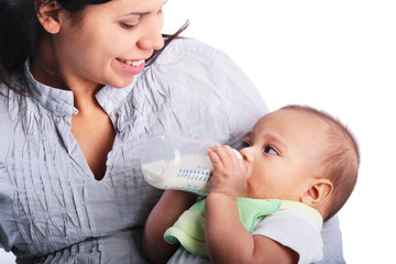 Happy mother feeding formula to baby child